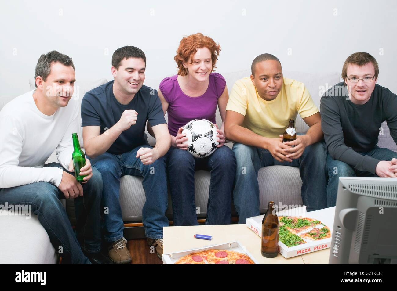 Friends with football, beer & pizza sitting in front of TV - Stock Image