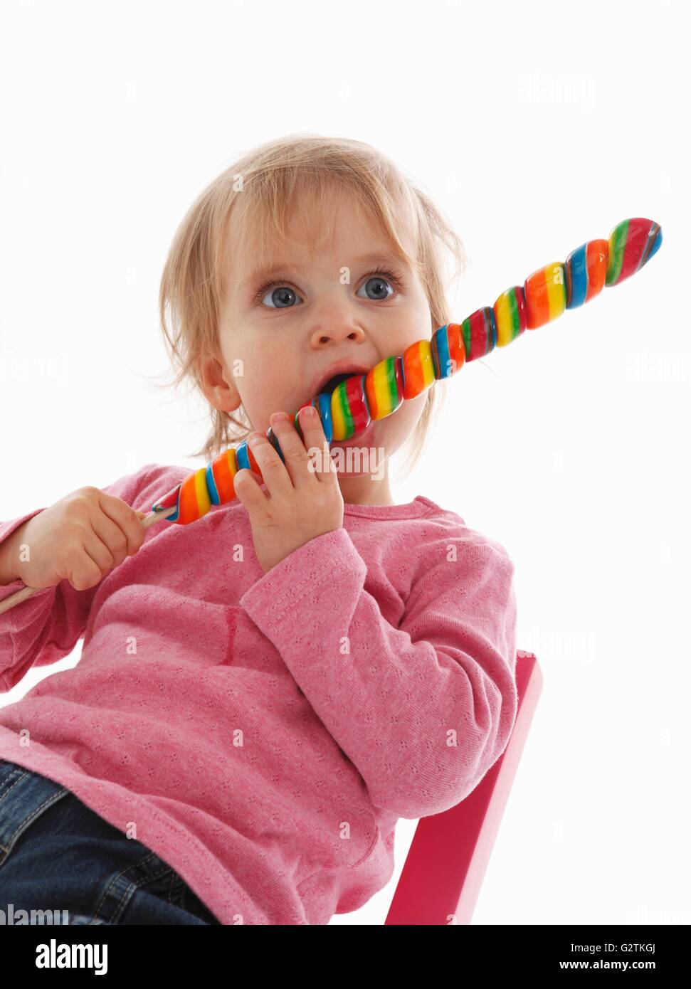A small child eating a giant lolly - Stock Image