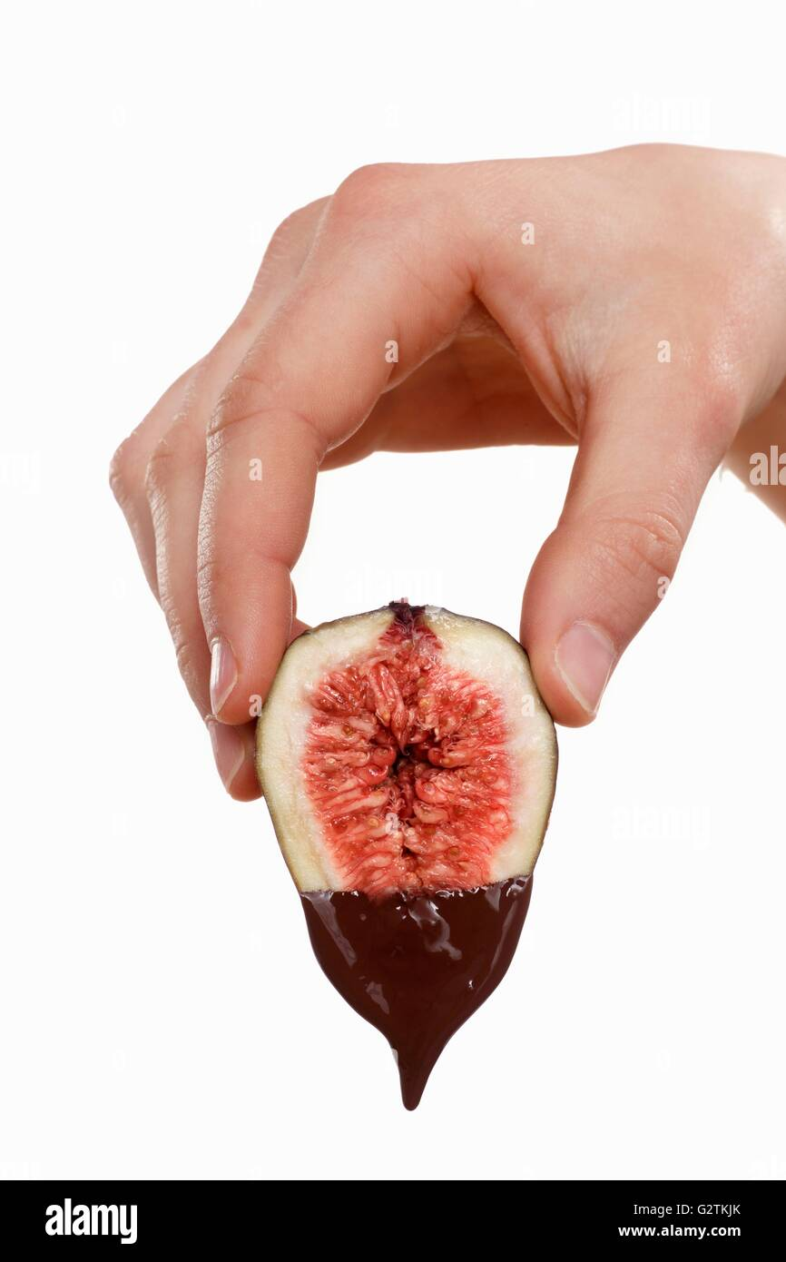 Hand holding a fig dripping with melted chocolate Stock Photo