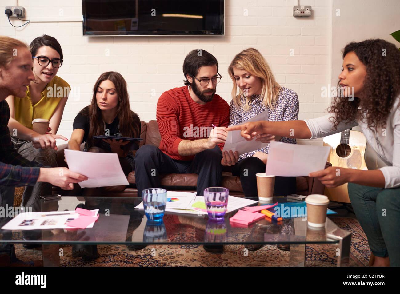 Designers Sitting On Sofa Having Creative Meeting In Office - Stock Image