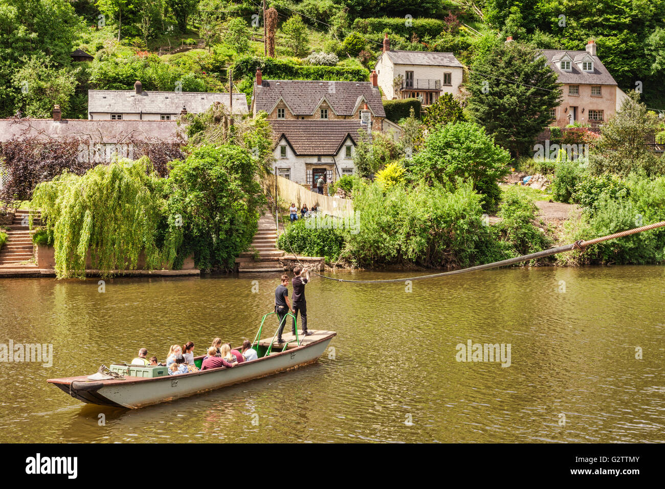 People crossing the River Wye on the ancient Hand Ferry at Symonds Yat, Gloucestershire, England, UK - Stock Image