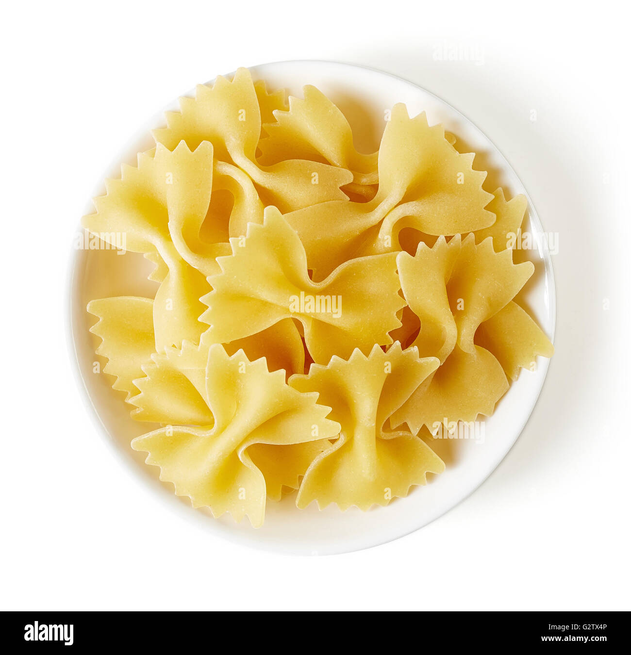 bow tie pasta in bowl, isolated on white background, top view - Stock Image