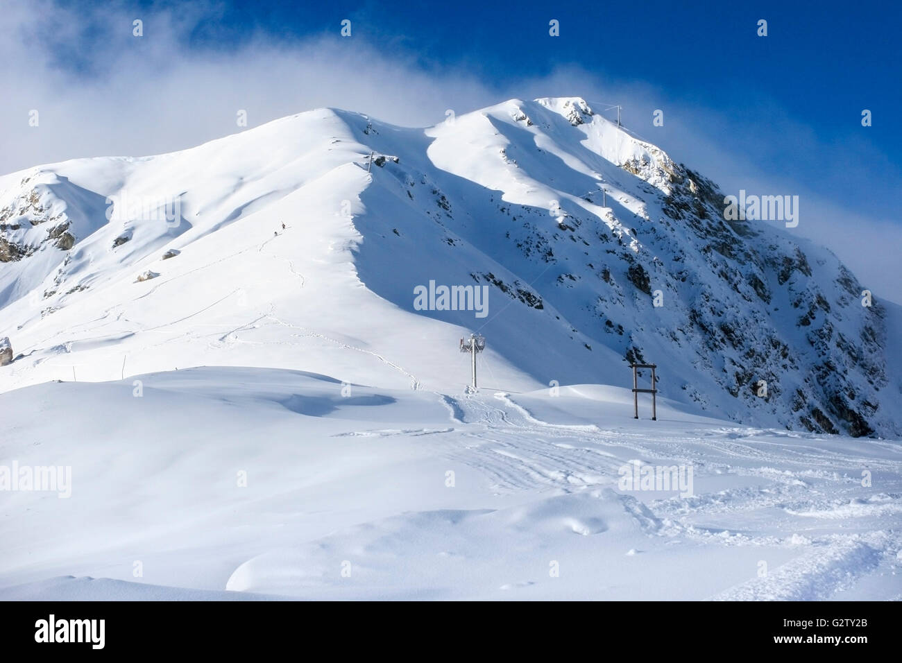 Les Arcs 2000 ski area in France, with two skiers making their way to the top on foot for an amazing off-piste run - Stock Image