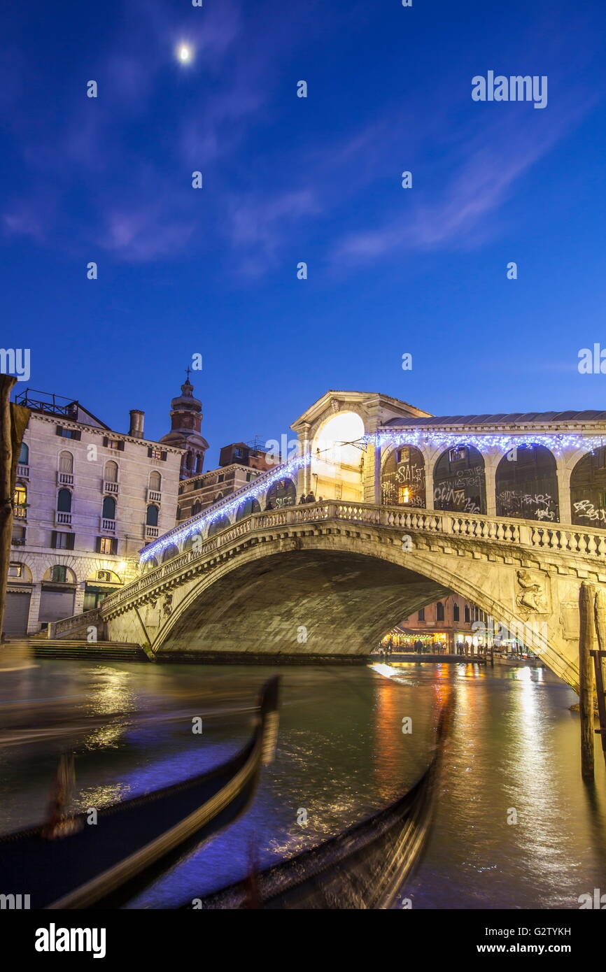 Night view of Rialto Bridge and the typical gondolas in the canal Venice Veneto Italy Europe - Stock Image