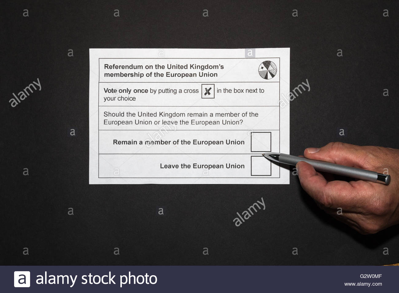 UK EU referendum ballot paper showing a hand holding a pen hovering between the Leave and Remain boxes on a black - Stock Image
