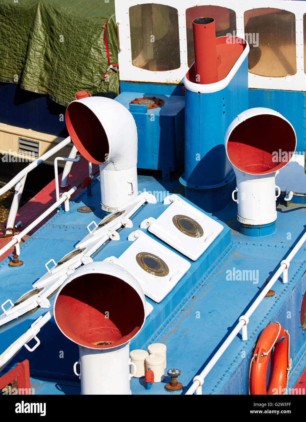 Colorful superstructure of small ship or boat painted in red, white and blue with traditional trumpet ventilation - Stock Image