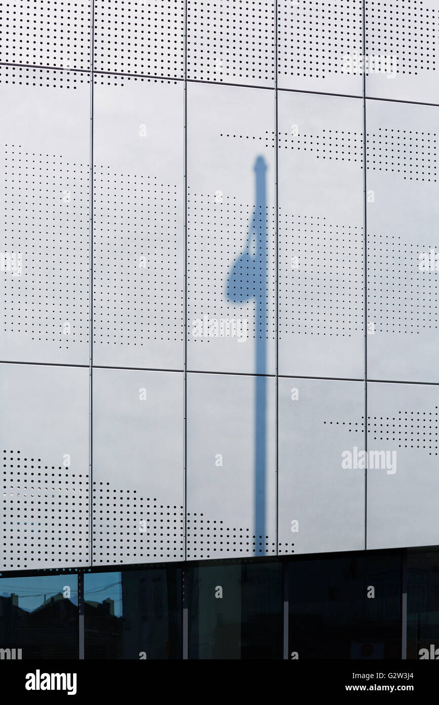 Shadow of a streetlight against the perforated metal cladding of the new West Yorkshire Joint Archives building Stock Photo