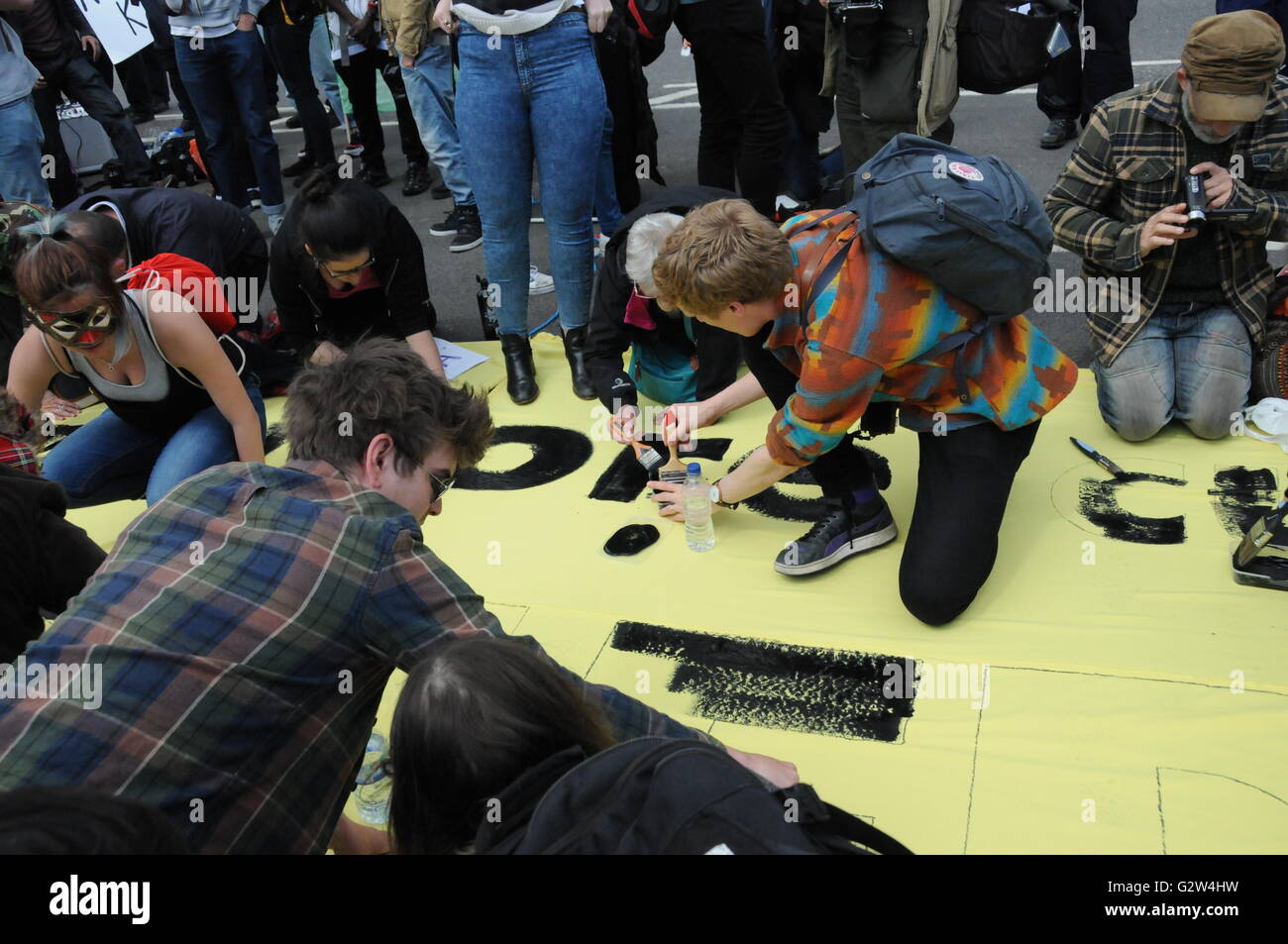 A group of protesters paint an anti austerity message on a banner, on London's Westminster Bridge - Stock Image
