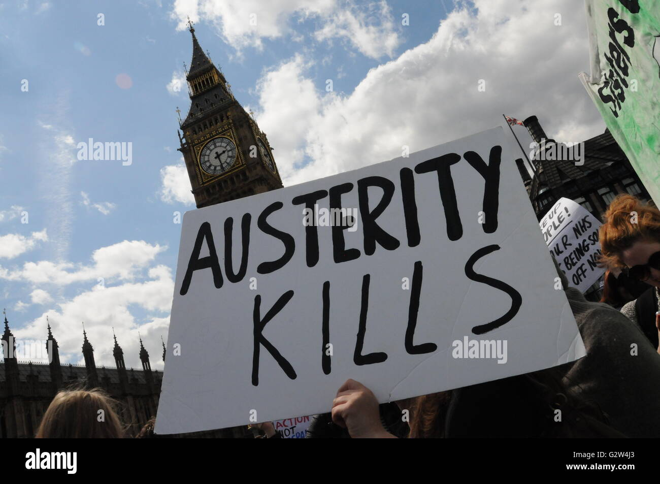 Anti-austerity protesters hold up a placard in front of Big Ben, London. - Stock Image
