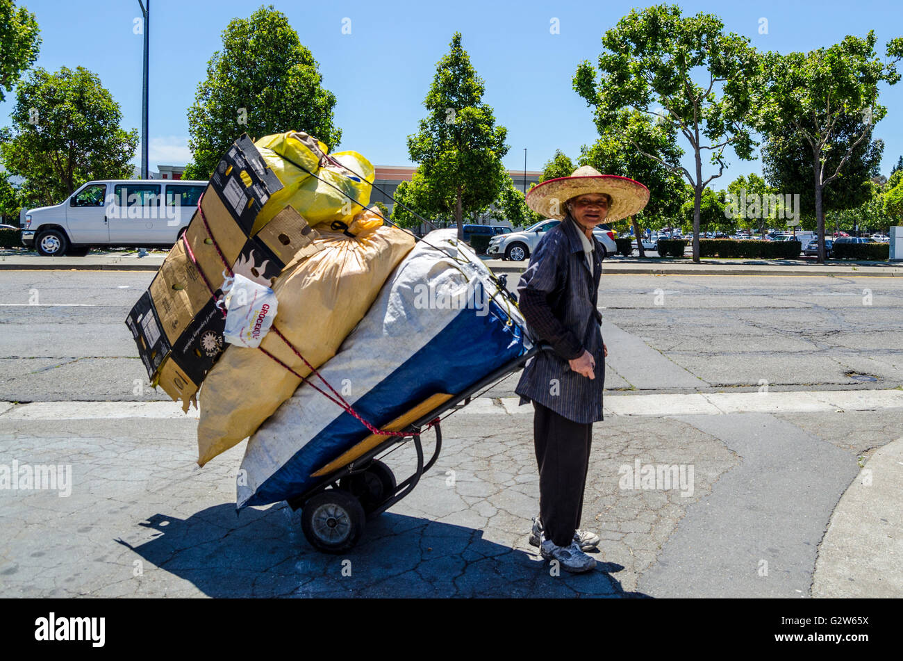 A hard working Asian man collecting recyclables in San Leandro California - Stock Image