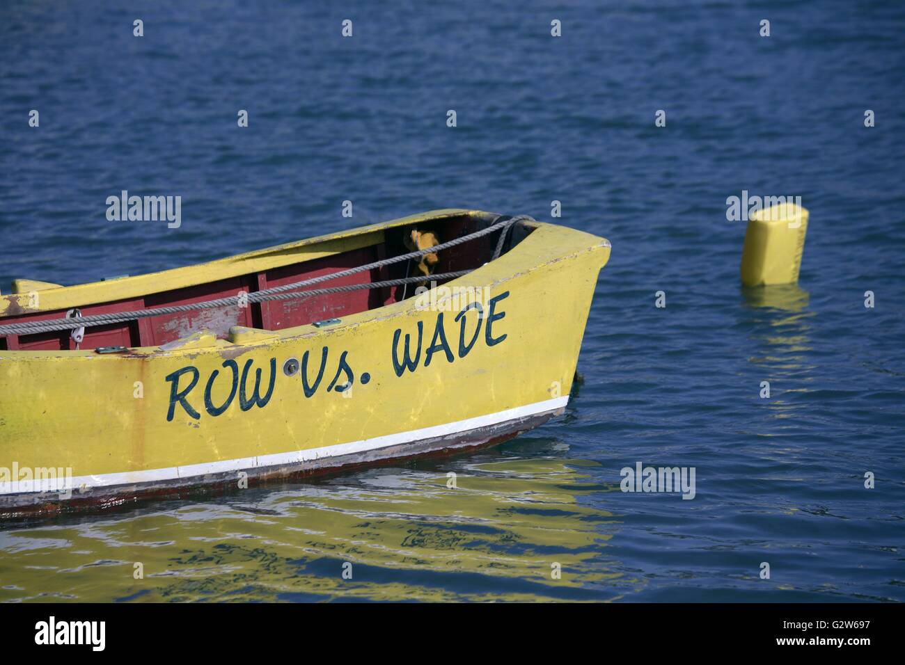 a rowboat tender moored with the name row vs wade in reference to