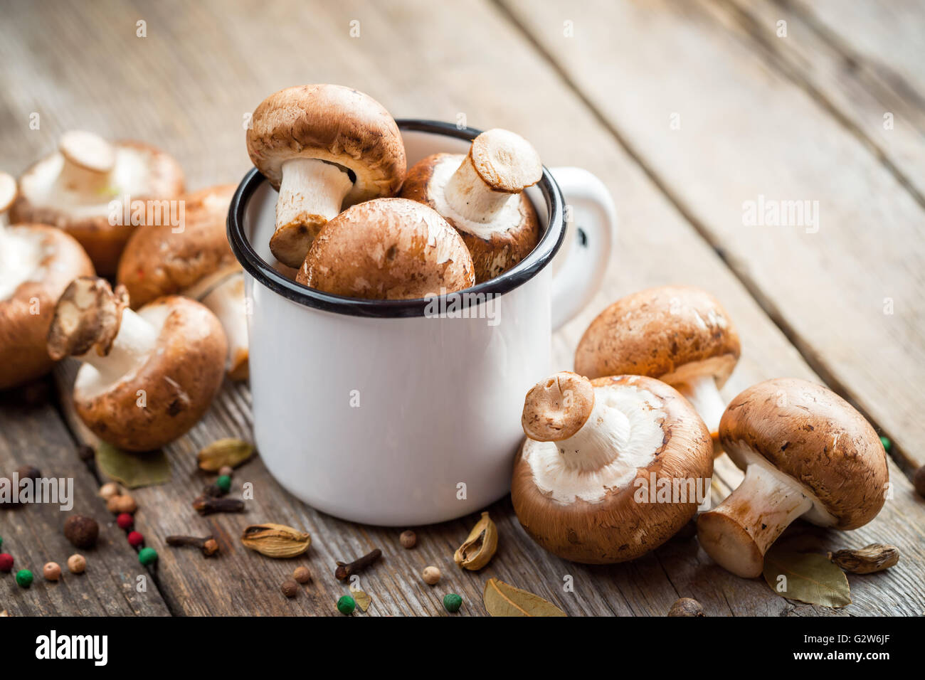 Mushrooms champignons in mug and spices on old wooden table. - Stock Image