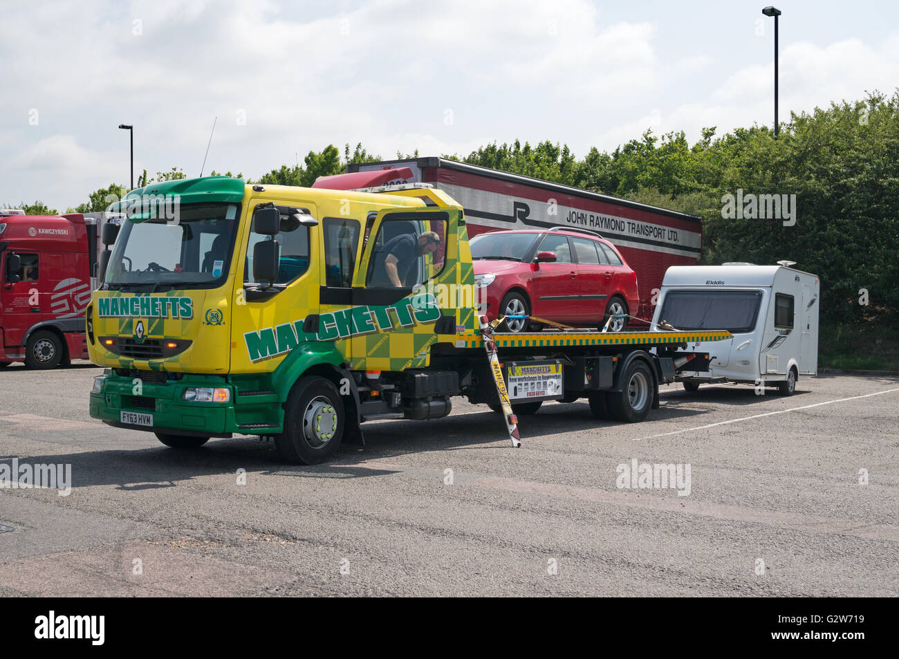 Broken down car on Manchetts Renault slidebed rescue truck with caravan in tow, Motorway service station, England, - Stock Image