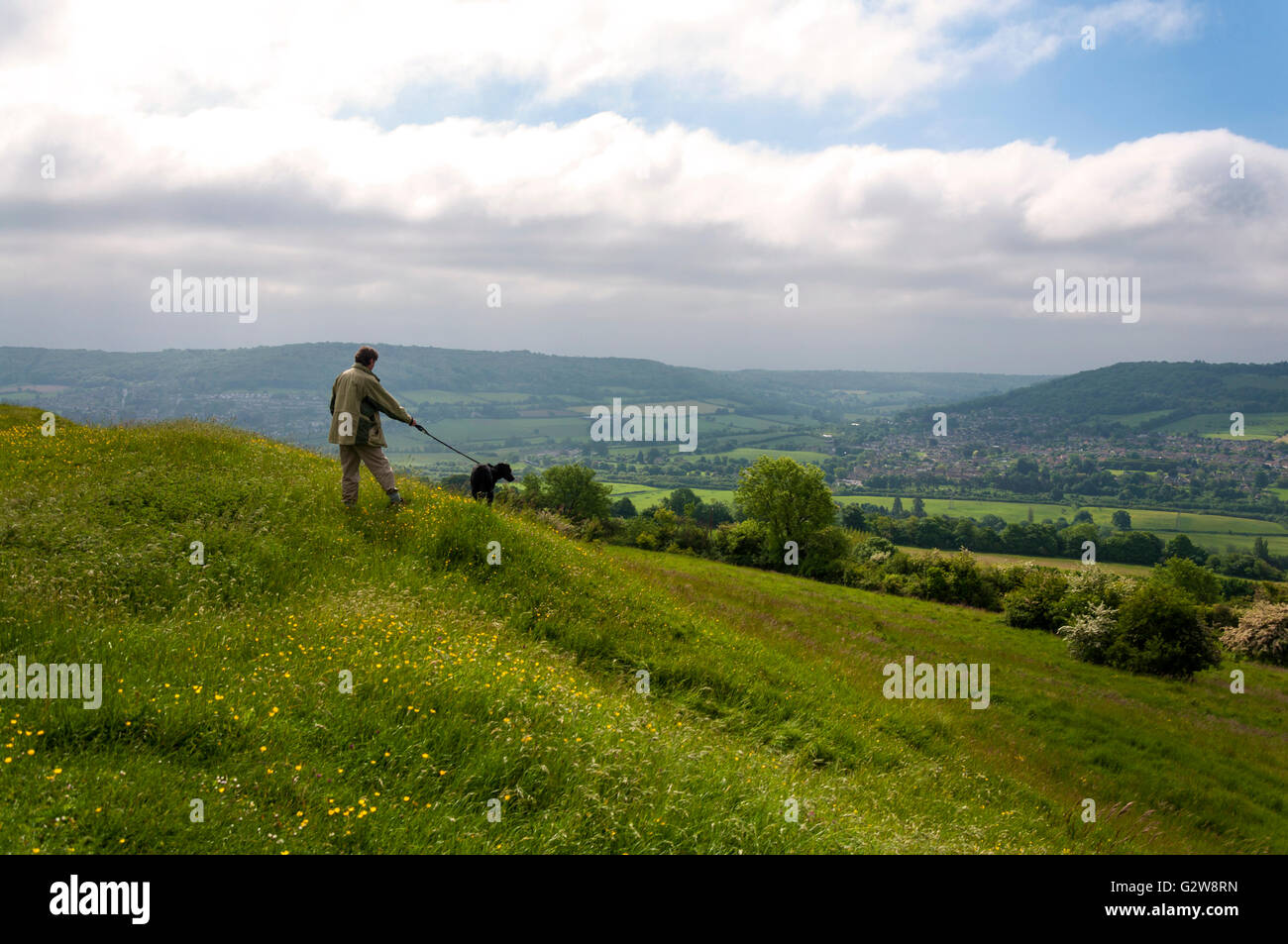 Little Solsbury Hill, Batheaston, Somerset. UK weather. 3rd June 2016. A dog walker admires the view from atop the Stock Photo