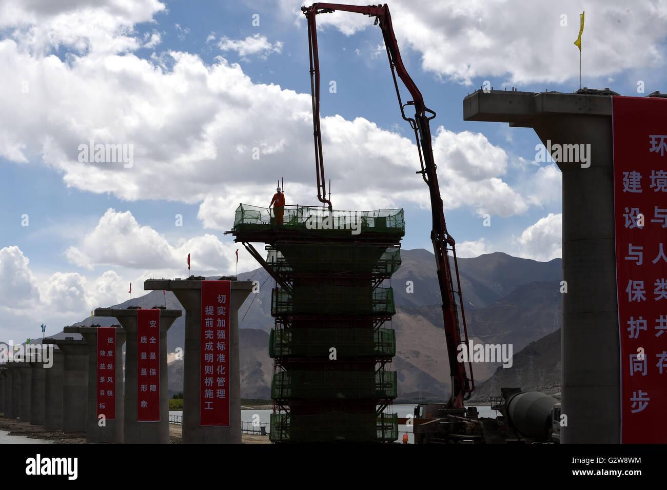 Lhasa, China's Tibet Autonomous Region. 2nd June, 2016. A worker checks concrete pouring on a pier of Mingze - Stock Image