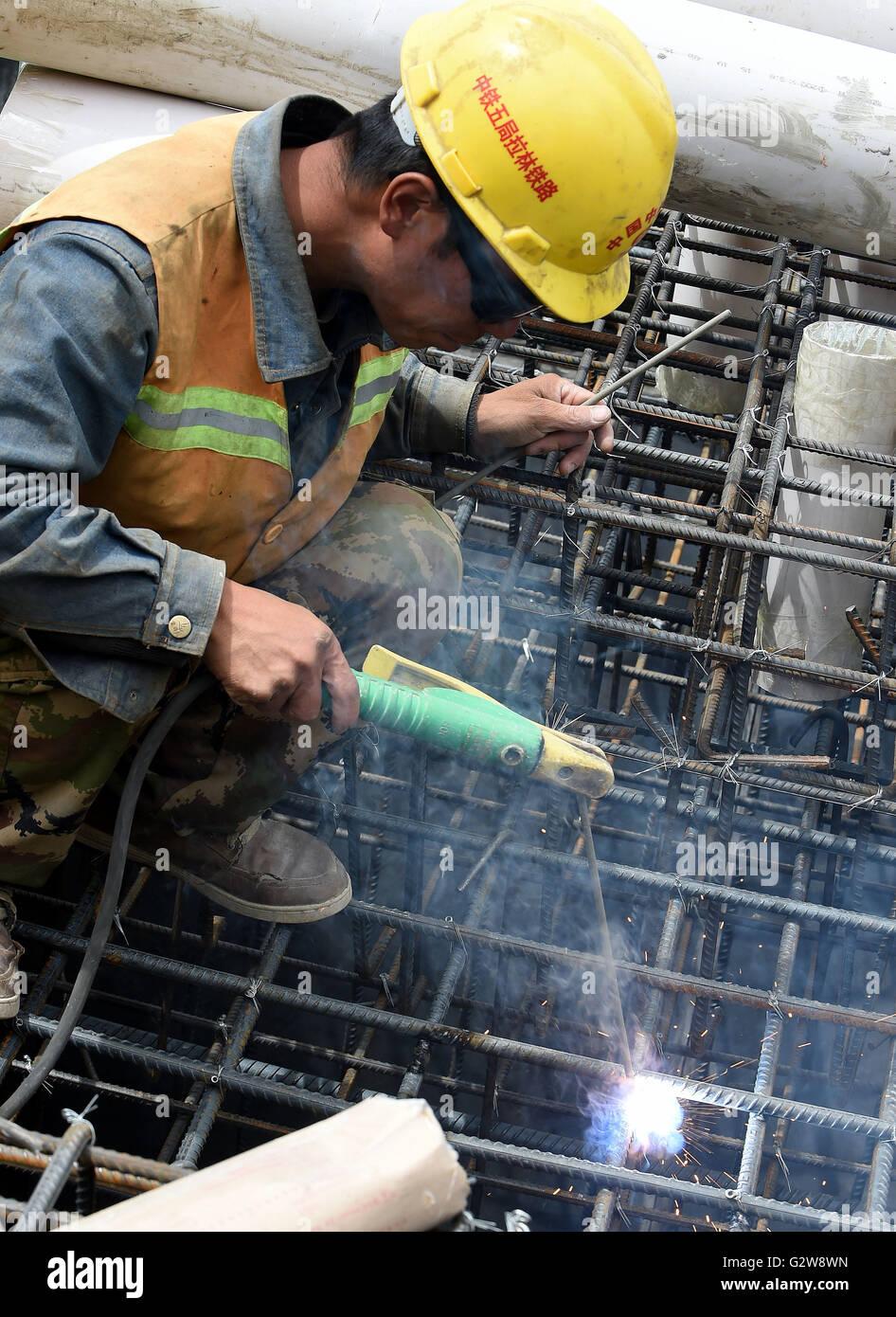 Lhasa, China's Tibet Autonomous Region. 2nd June, 2016. A worker welds on a pier of Mingze Bridge under construction - Stock Image