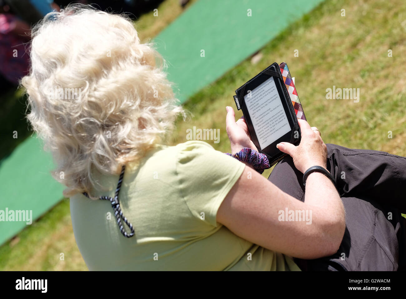 Hay Festival, Wales, UK - June 2016 -  A woman sits and reads her ebook reader tablet on the Hay Festival lawns. - Stock Image