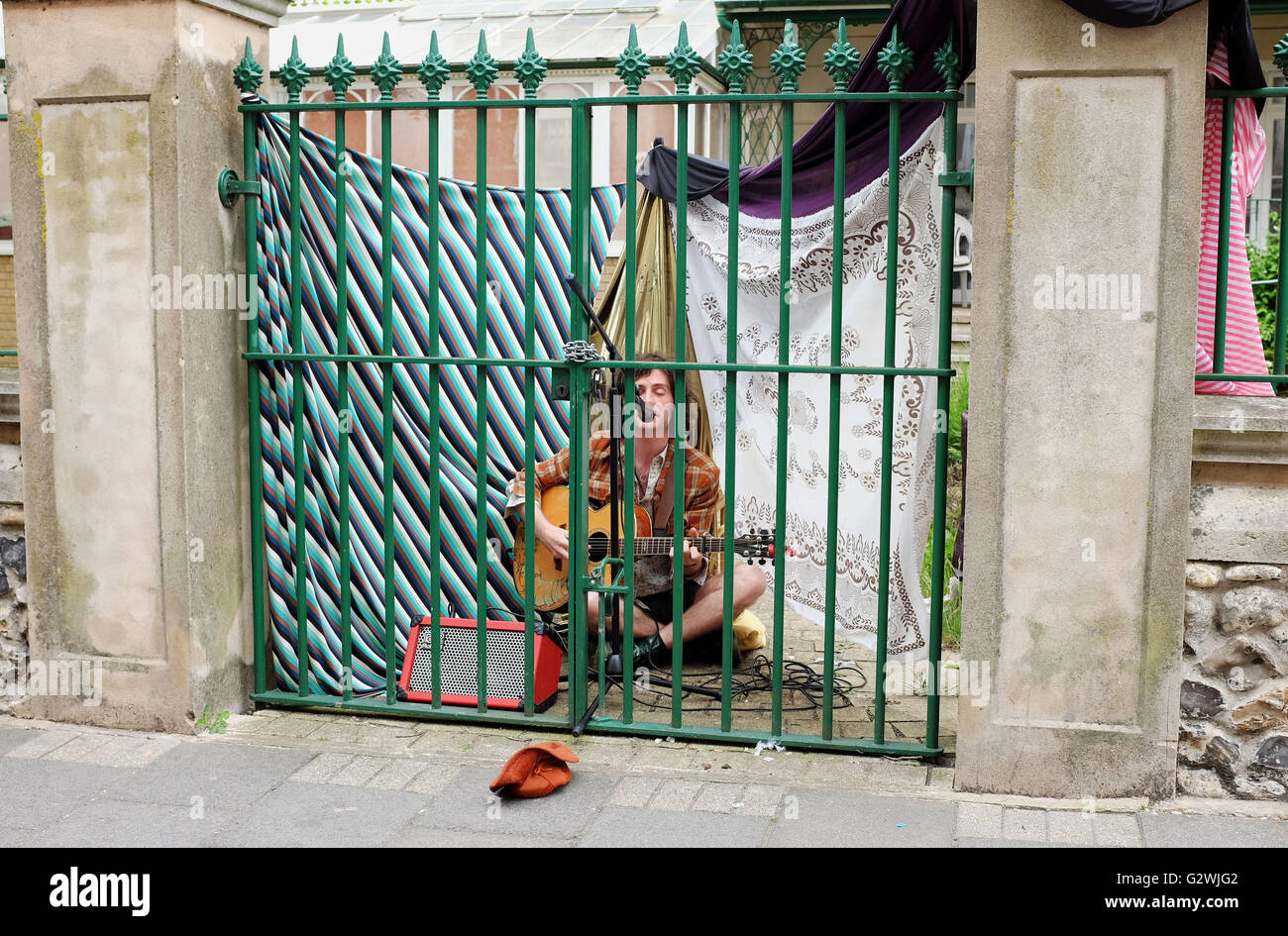 Brighton UK 4th June 2016 - An unusual busking singer guitarist performs behind a locked gate at Kemptown Carnival - Stock Image