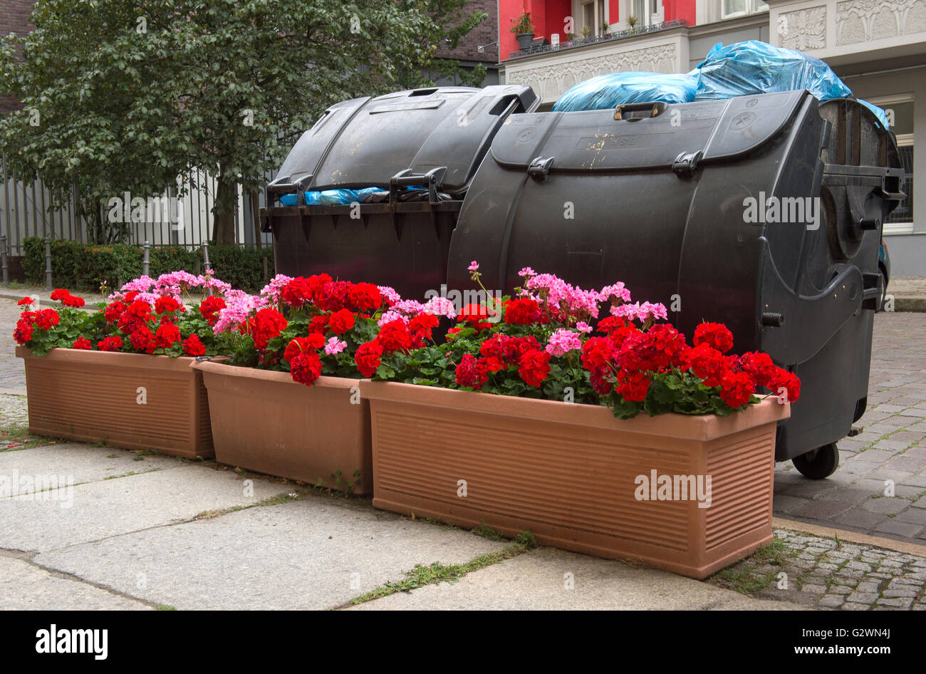 Berlin, Germany, Flower boxes are facing trash cans - Stock Image