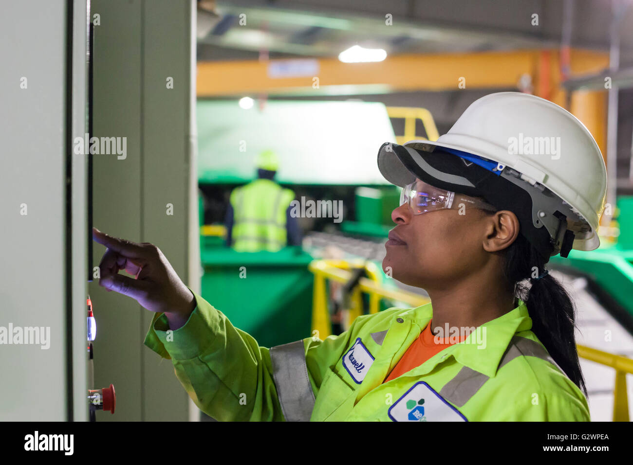 Southfield, Michigan - A worker operates a control panel for machinery at the ReCommunity materials recovery facility. - Stock Image