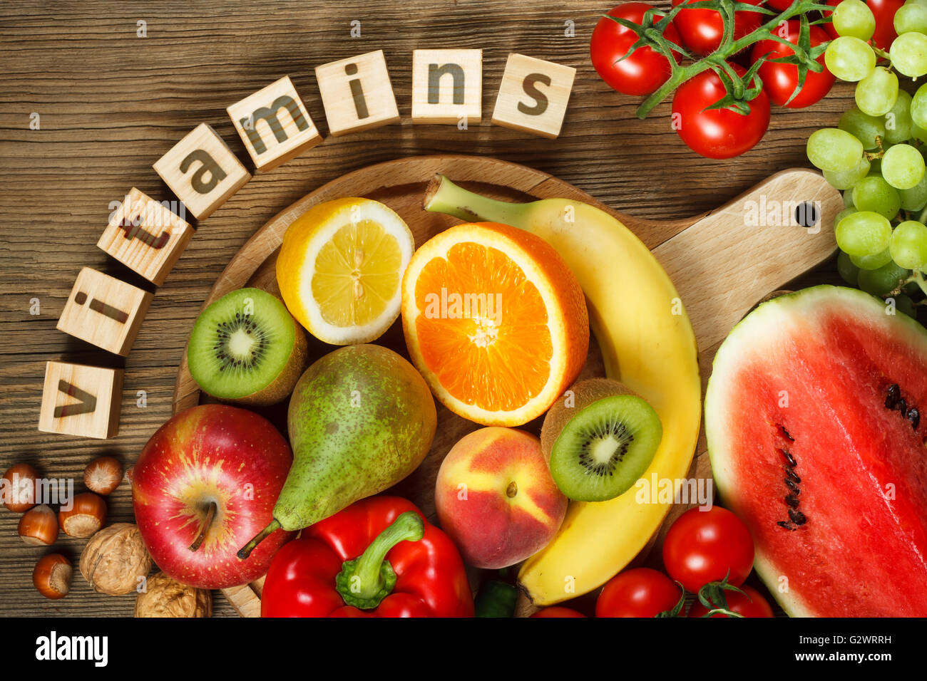 Vitamins in fruits and vegetables. Natural products rich in vitamins as oranges, lemons, red pepper, kiwi, tomatoes, - Stock Image
