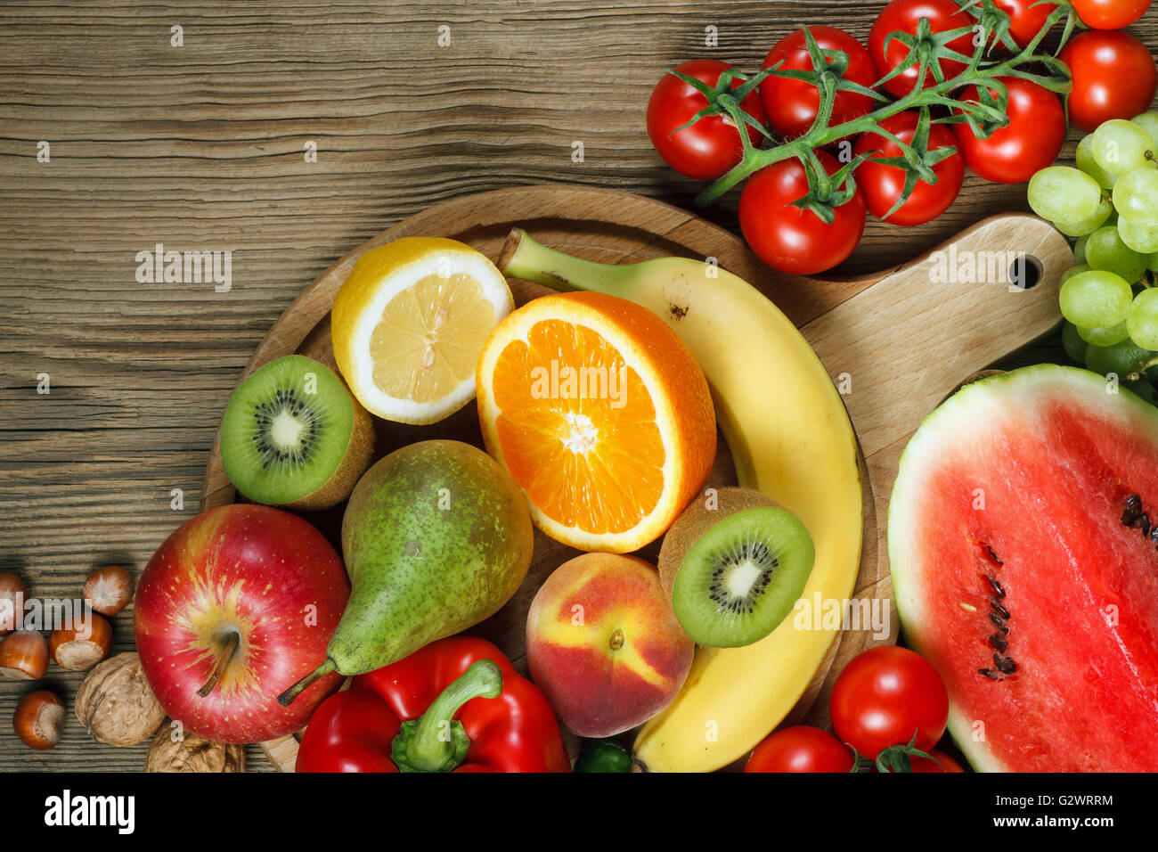 Vitamins in fruits and vegetables. Natural products rich in vitamins as oranges, lemons, red pepper, kiwi,tomatoes, - Stock Image