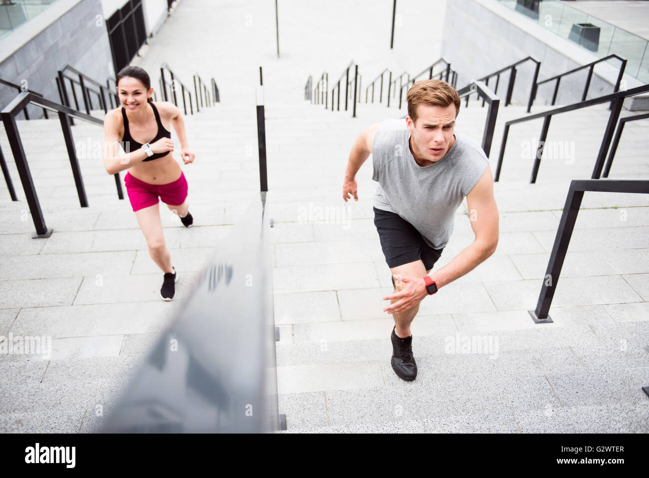 Man and woman running on the stairs - Stock Image