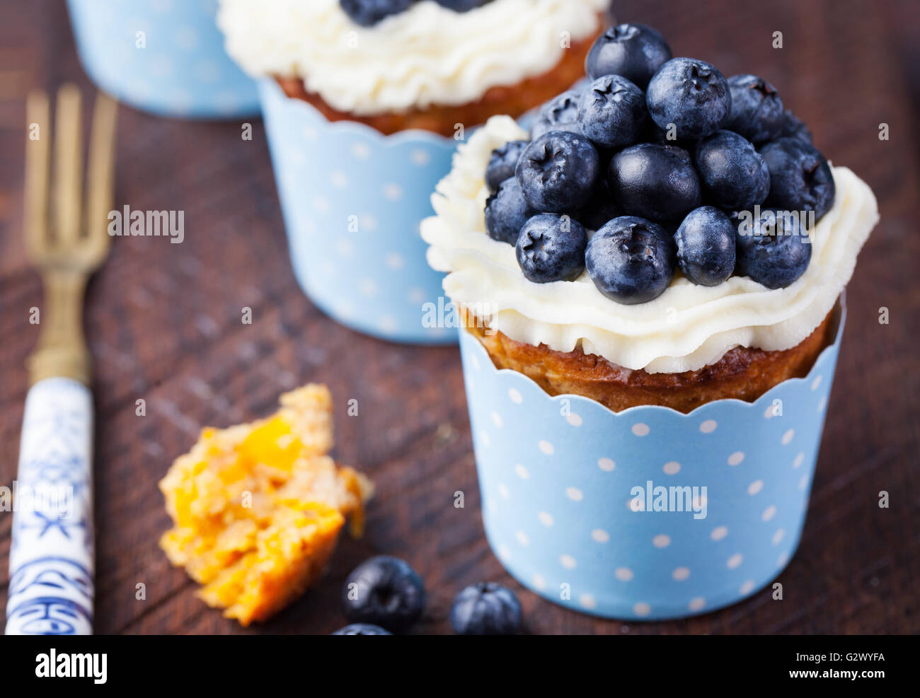 Pumpkin cupcakes with cream cheese, blueberries - Stock Image