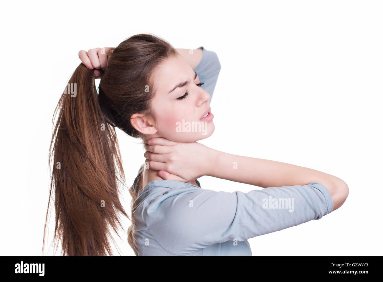 Young woman suffer from neck pain - Stock Image