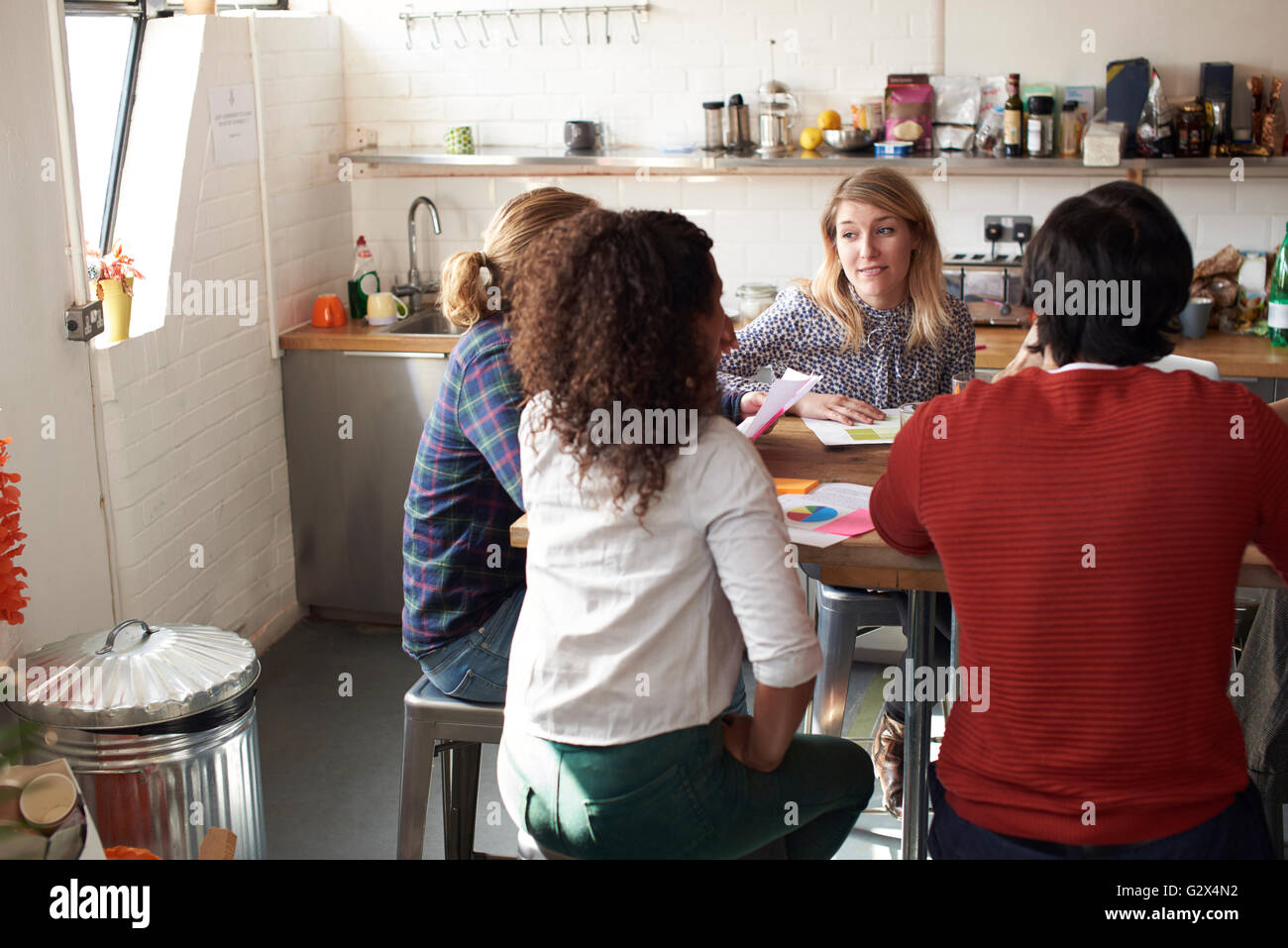 Group Of Designers Meeting Around Table In Modern Office - Stock Image