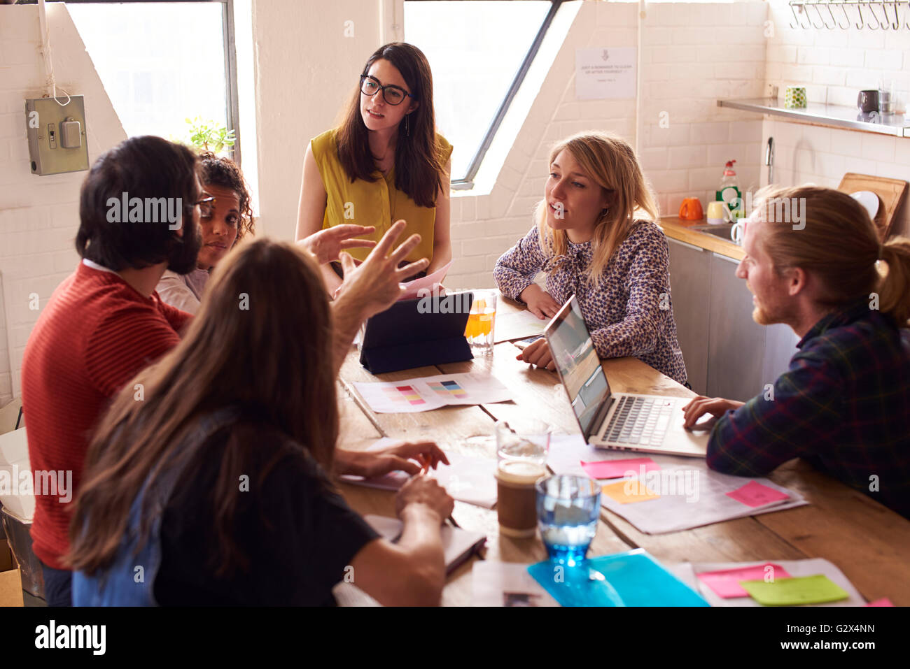 Female Manager Leads Meeting Around Table In Design Office - Stock Image