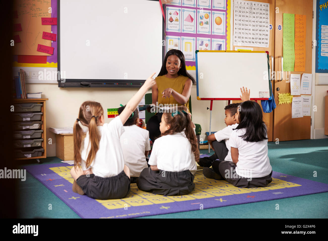 Teacher Asks Elementary School Pupils Question In Classroom - Stock Image