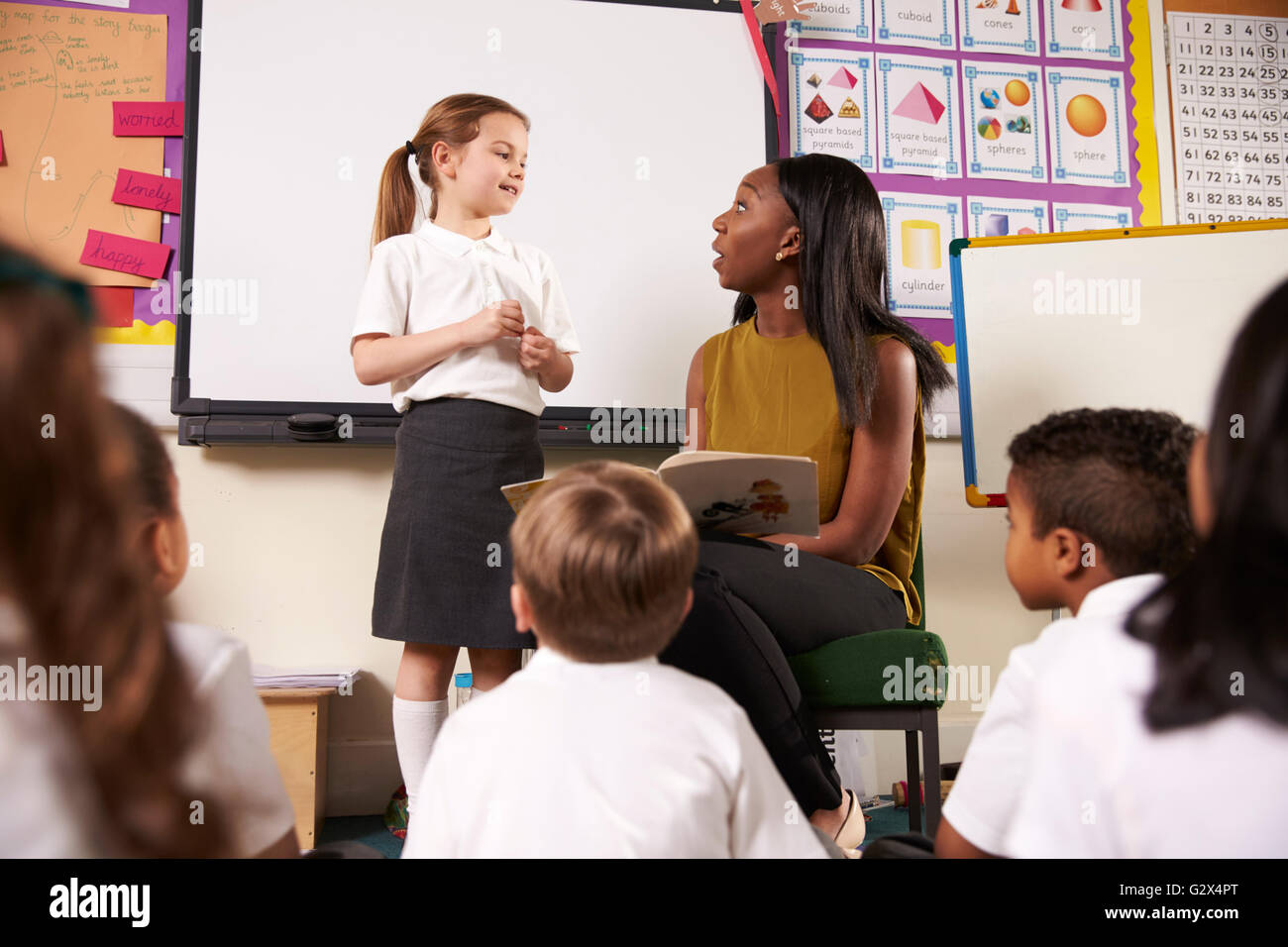 Female Elementary Pupil Reading In Front Of Class - Stock Image