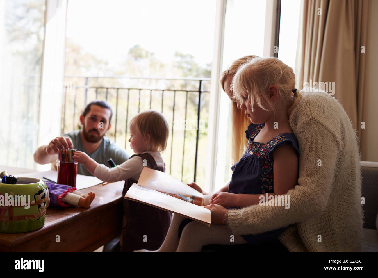 Family Drawing Pictures And Reading At Home Together - Stock Image