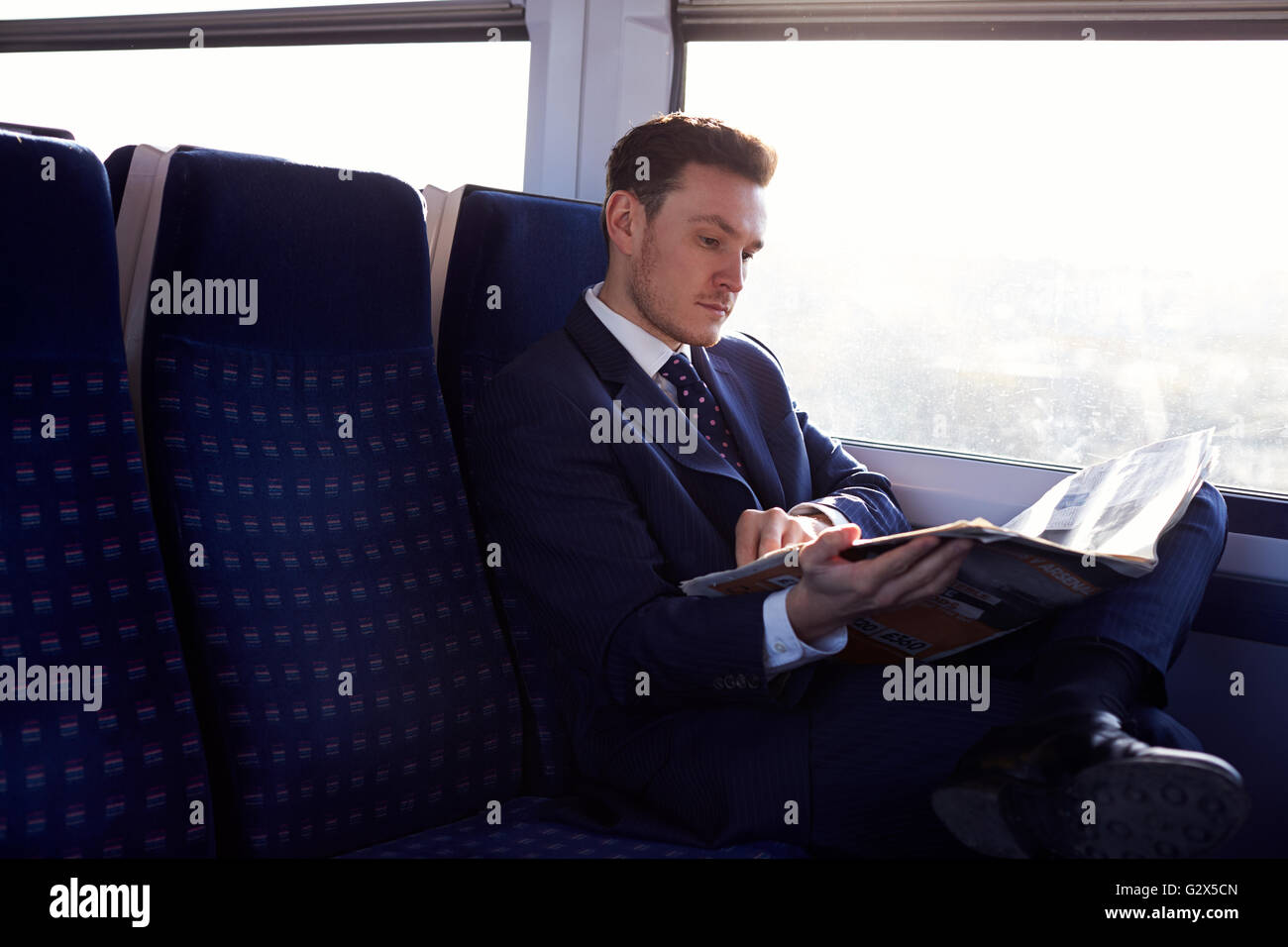 Businessman Commuting To Work Reading Newspaper On Train - Stock Image