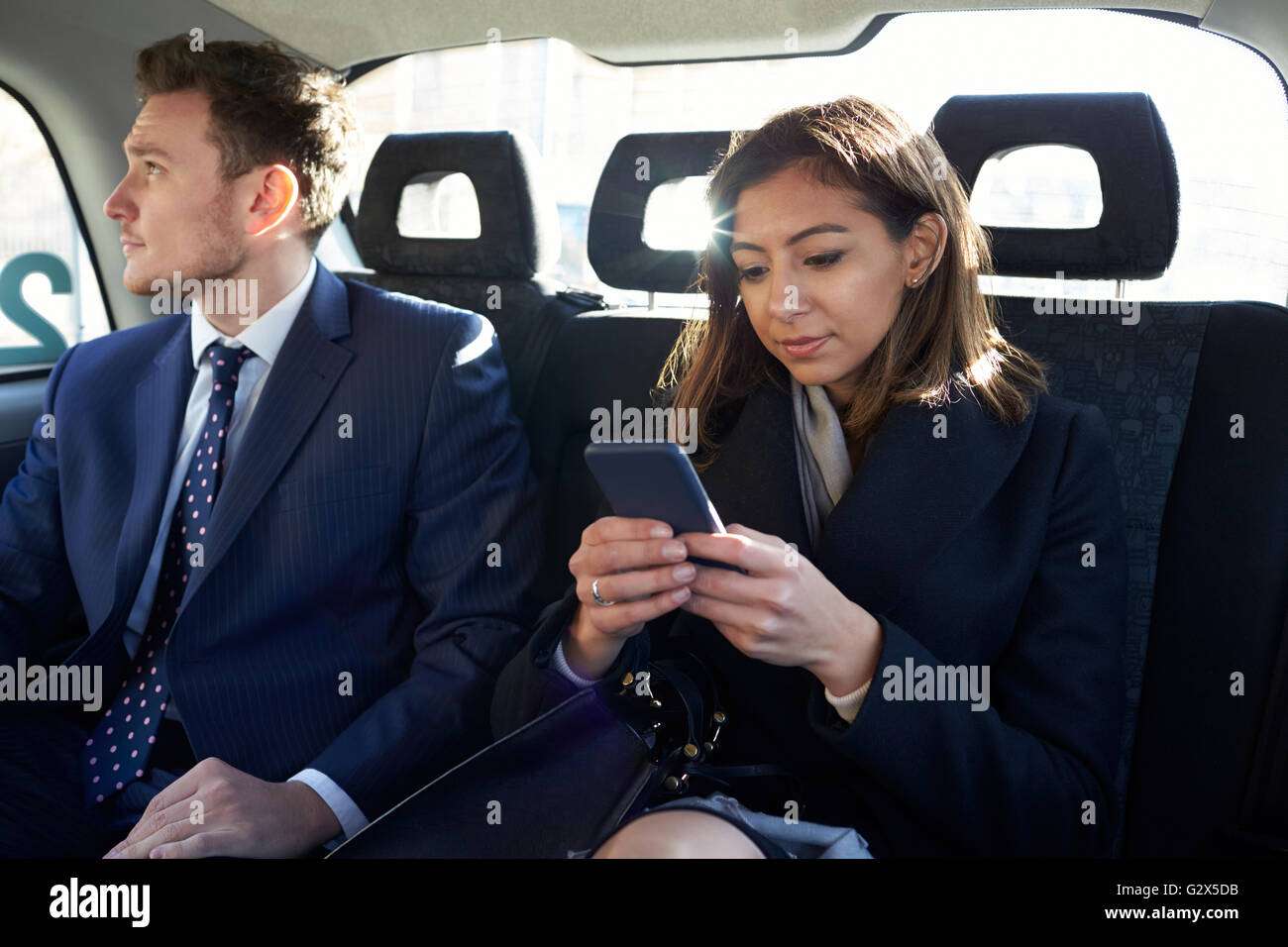 Businesspeople Travelling In Taxi Using Mobile Phones - Stock Image