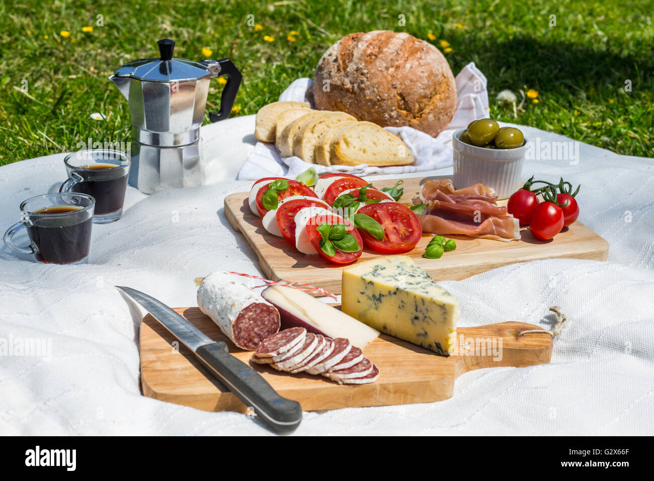 Outdoor picnic consisting of rustic bread, ciabatta, espresso in cups, olives, tomatoes, parma ham, mozzarella - Stock Image