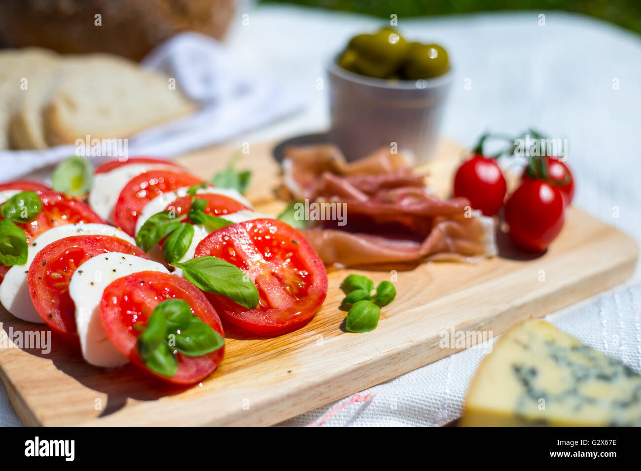 A picnic of tomato and mozzarella salad, parma ham, strawberries, olives and espresso pot in a park - Stock Image