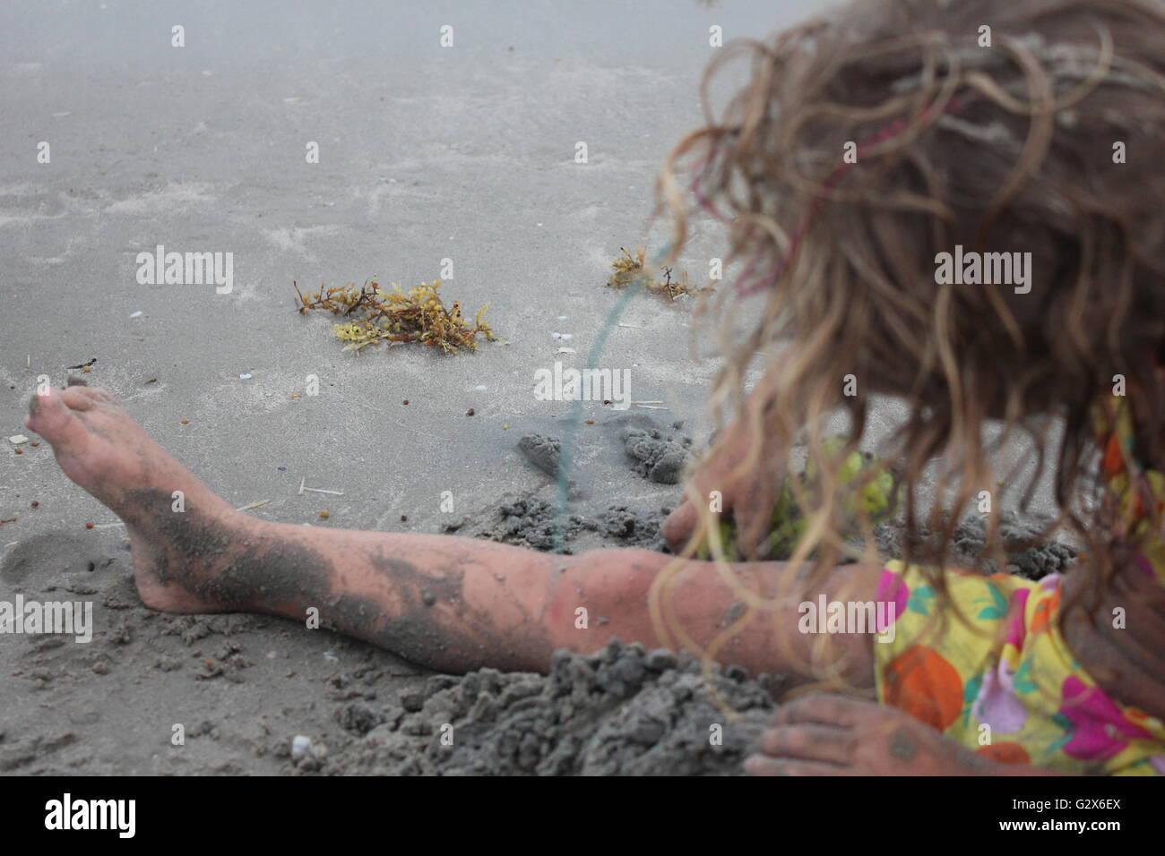 Little Girl Building Castles in the Sand - Stock Image