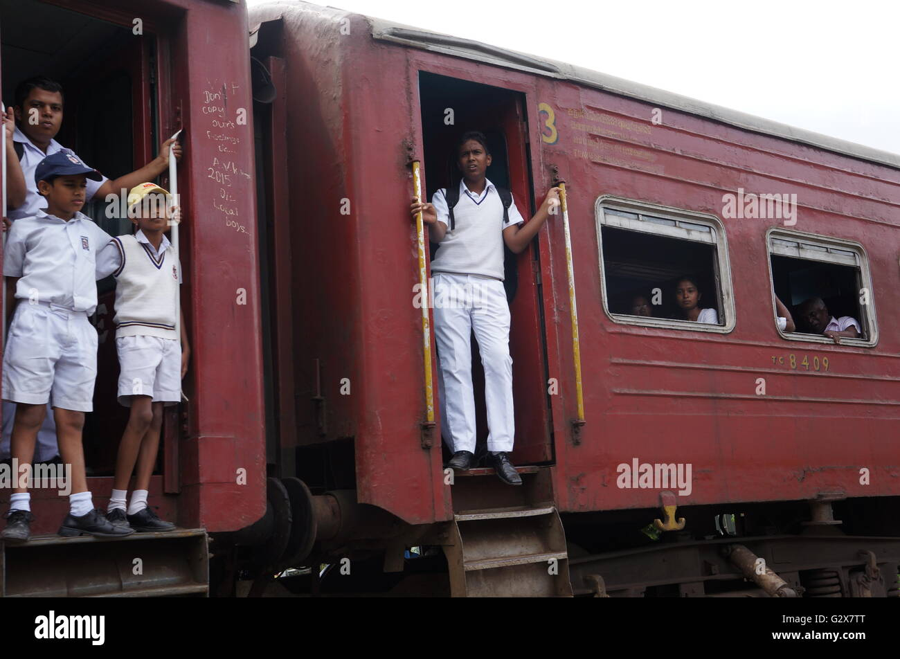 Young students in uniform on their way back from school standing on the platforms of an old train, Kandy, Sri Lanka. Stock Photo