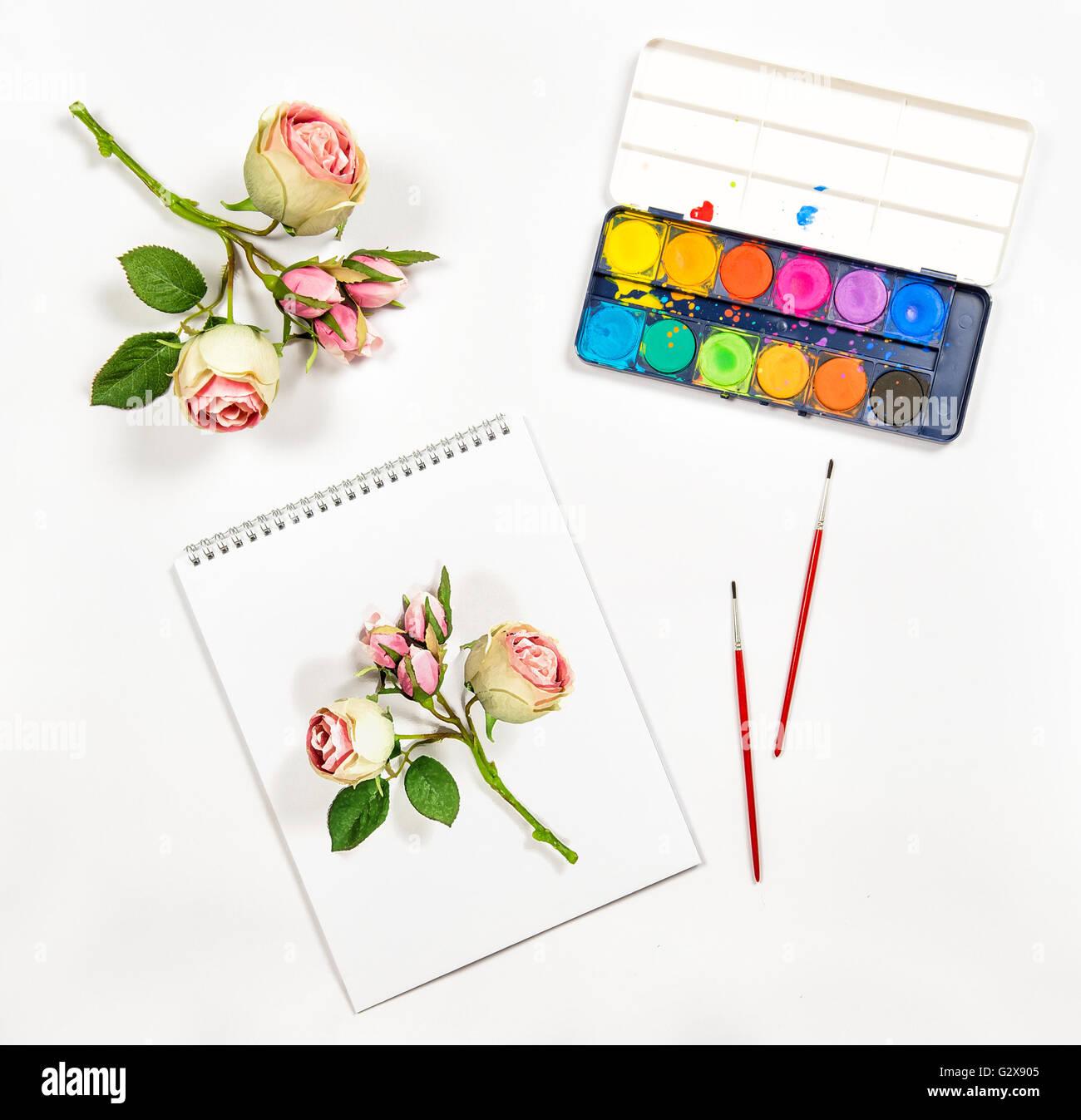 Sketchbook, watercolor, brushes, paper, rose flowers  Artistic Stock