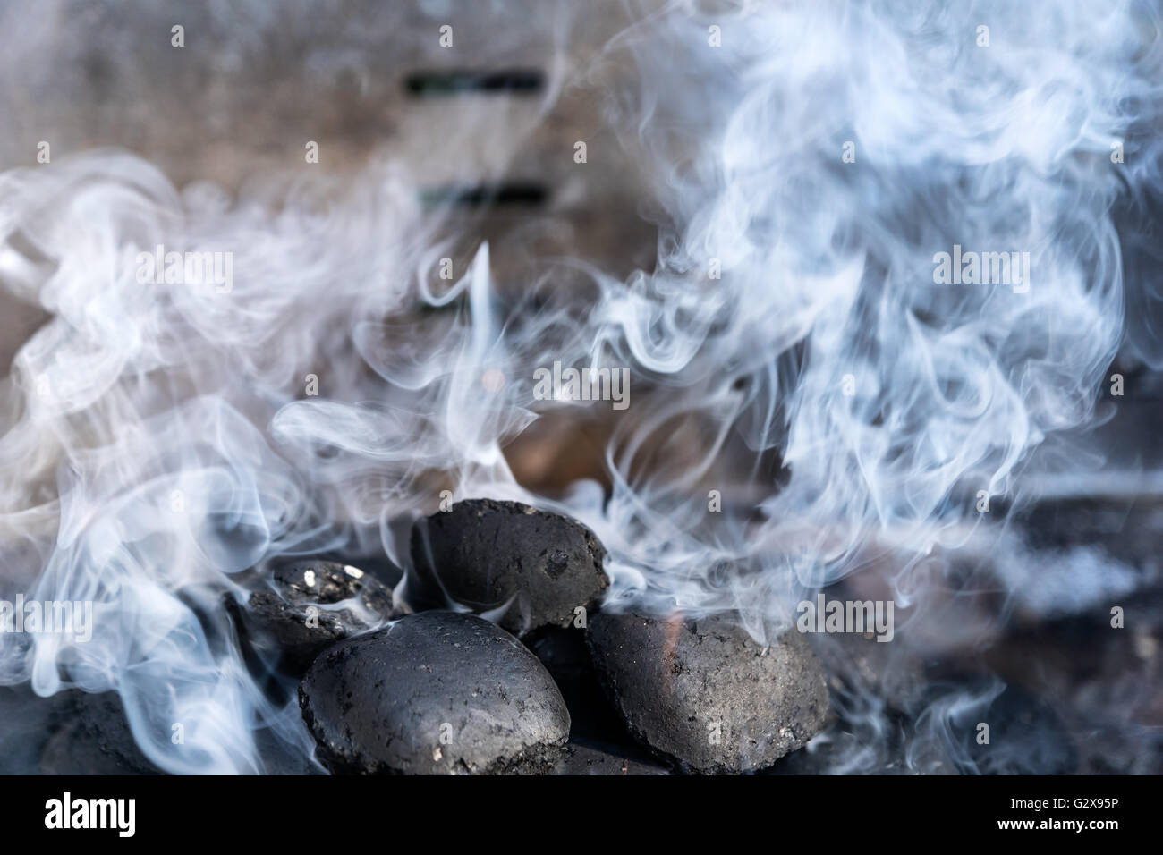 To light  coals in a barbecue grill with a lot of smoke - selected focus, narrow depth of field Stock Photo