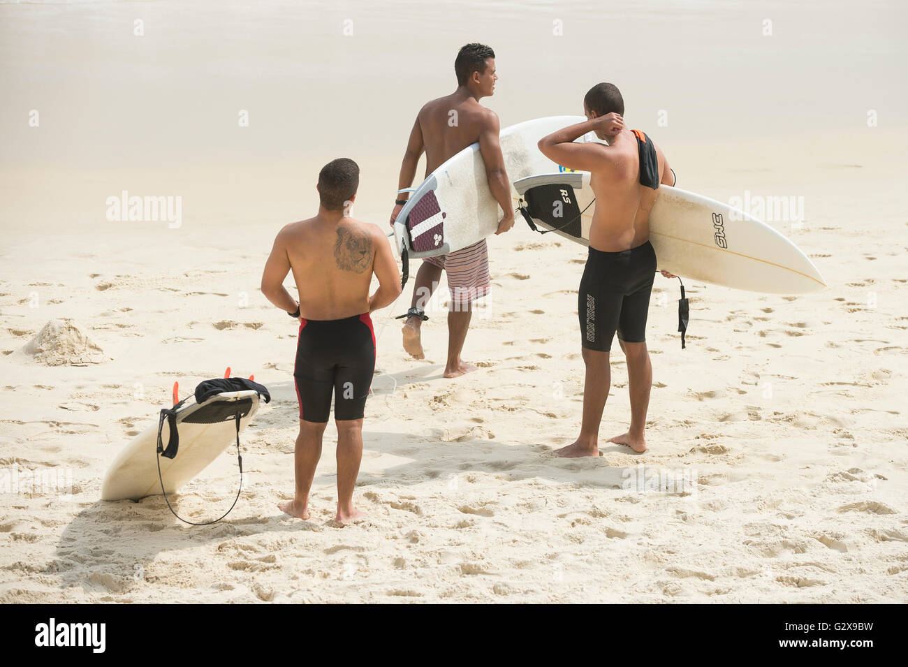 RIO DE JANEIRO - APRIL 3, 2016: Group of young Brazilian carioca surfers stand on Praia do Diabo surf beach at Arpoador. - Stock Image