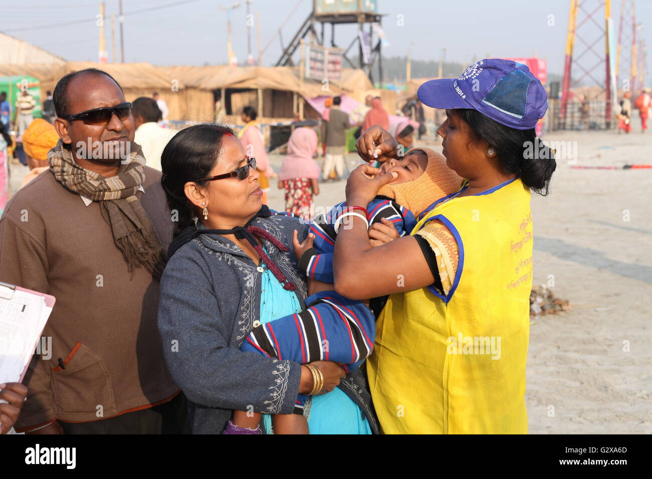 a health worker giving oral polio vaccine to a child during ganga sagar festival in west bengal - Stock Image