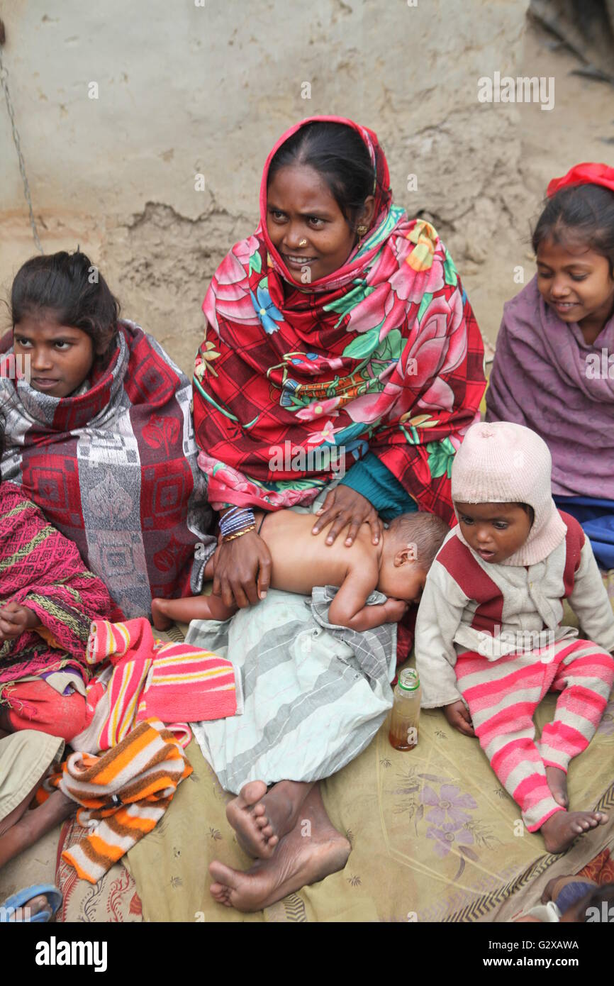 a tribal mother oil massaging her new born baby on a cold winter morning - Stock Image