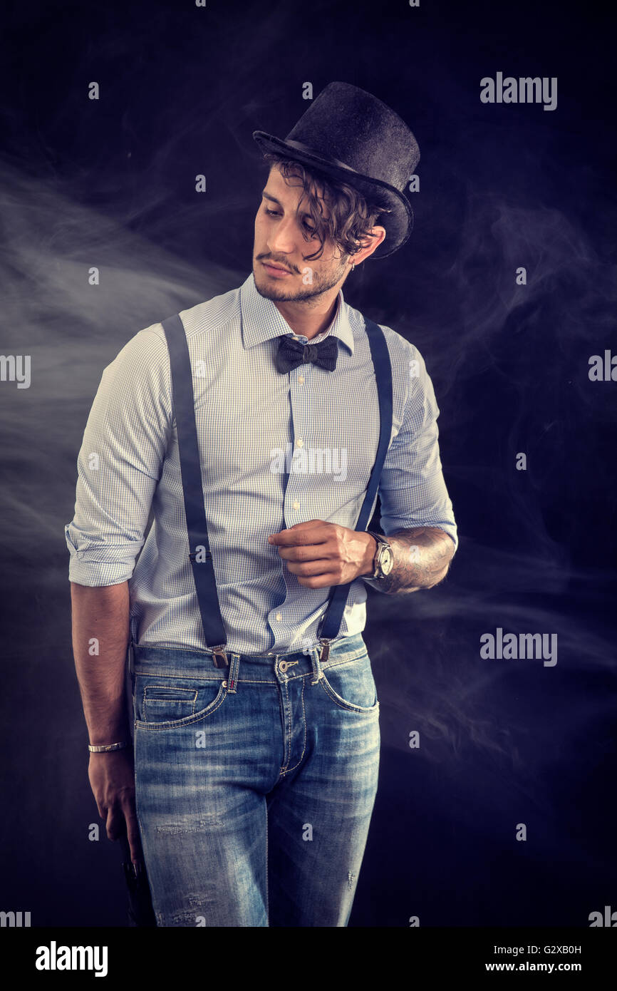 Portrait of brunette young man in glasses, bow-tie, suspenders and shirt looking at camera. Studio shot isolated - Stock Image