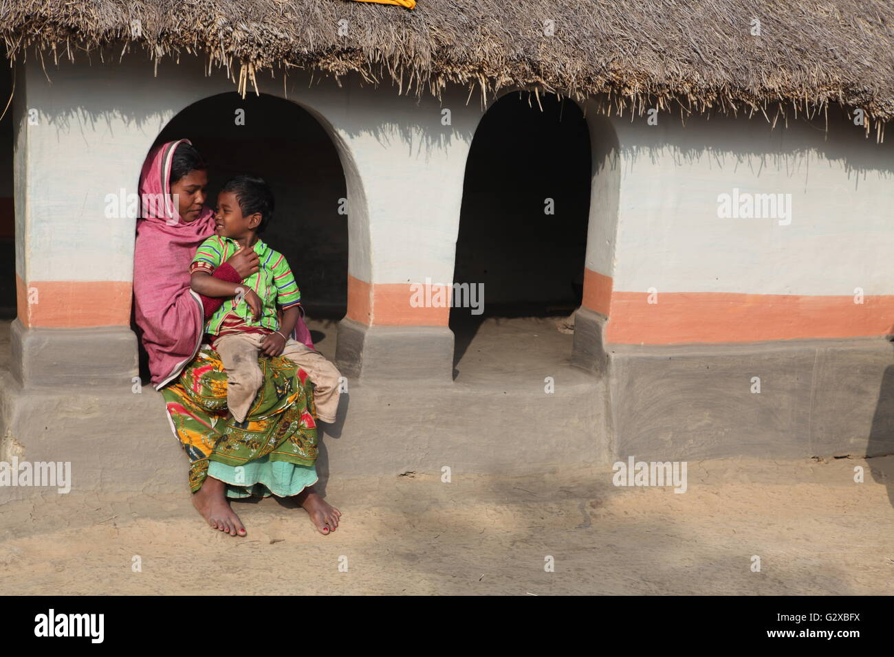 a tribal lady with her son at her beautiful mud hut in raiganj,west bengal - Stock Image