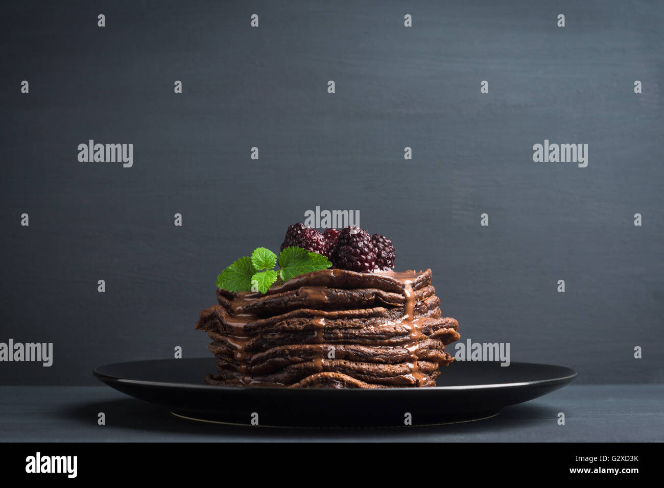 Stack of pancakes with fresh blackberries. Shallow depth of field. - Stock Image