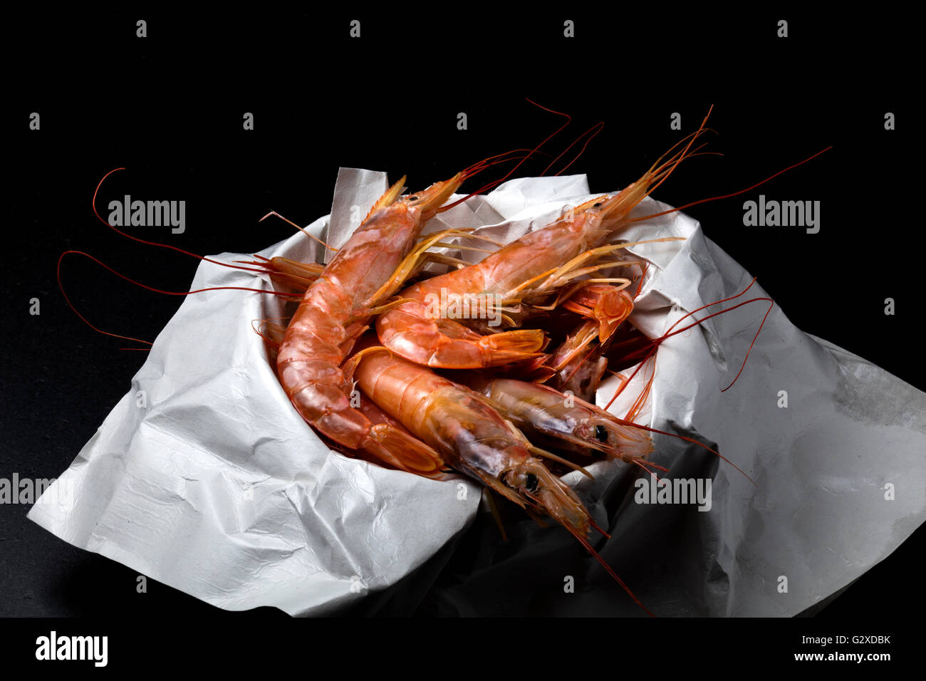 fresh prawn just bought in the market on a black stone. Free space on top - Stock Image