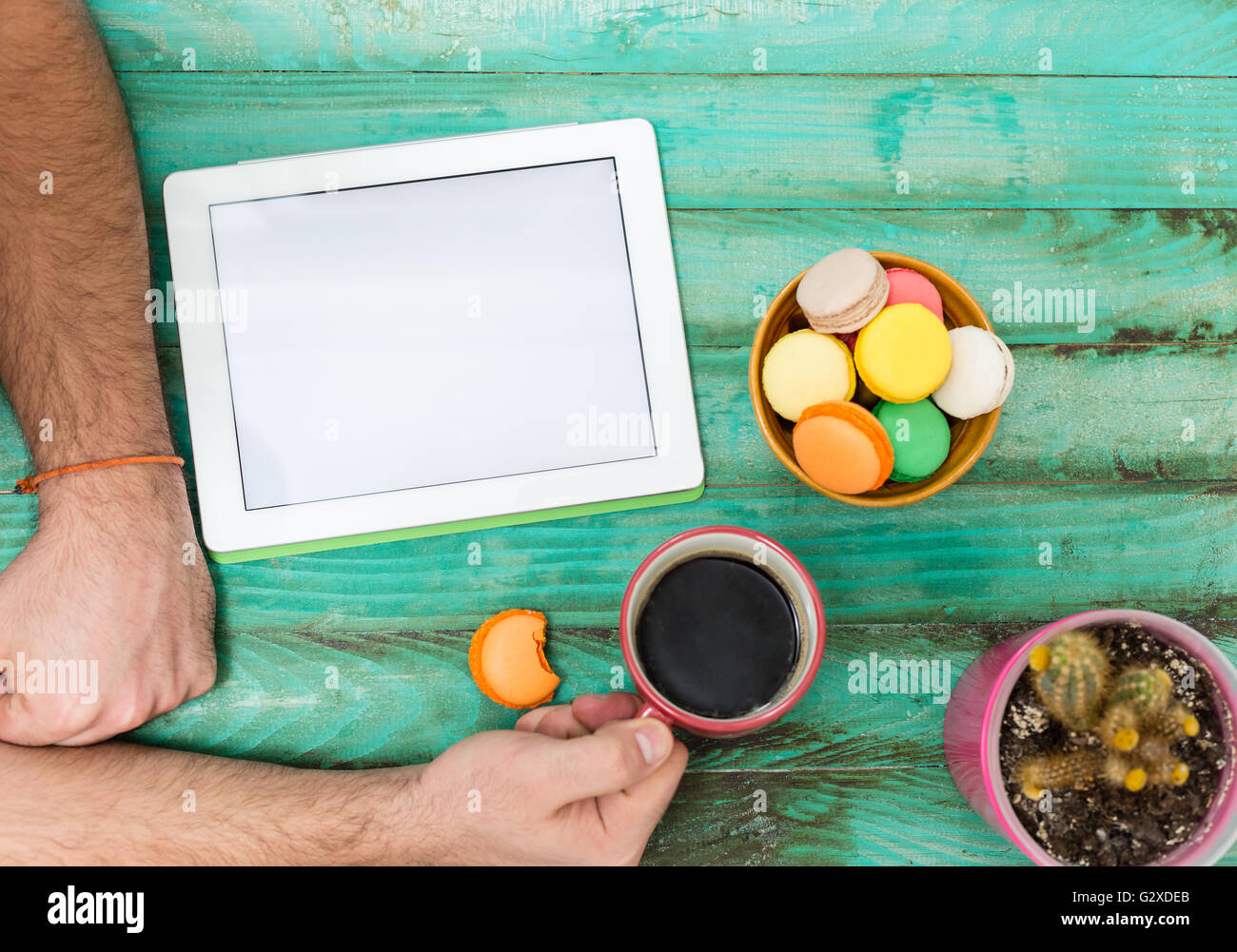Digital tablet computer with isolated screen in male hands over cafe background - cakae and cafee time - Stock Image
